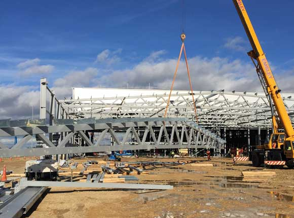 One of the large roof trusses is lifted into place