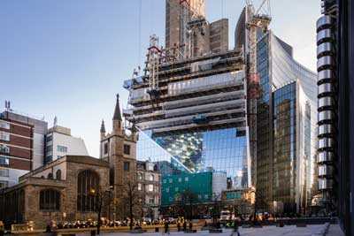 The glass cladding installation progresses behind the steel erection