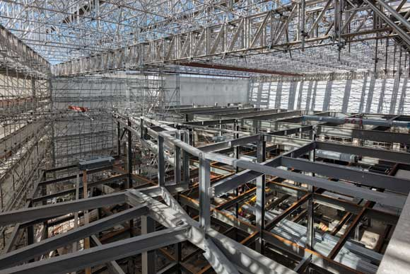 A scaffold system spans the project, helping to keep the site watertight, and supports two gantry cranes