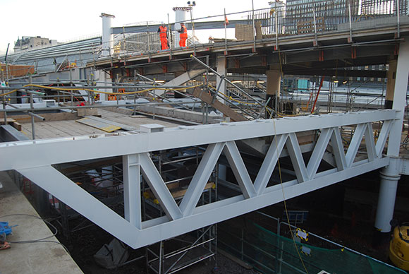 A large truss spans live rail lines and supports the new concourse building