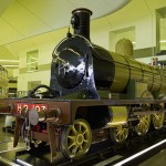 A locally built steam locomotive is supported on a large steel struss above first floor level