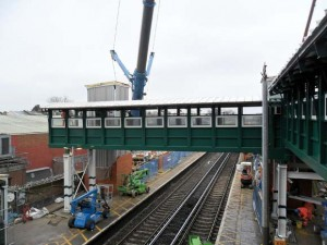 A large bridge section is lifted into place