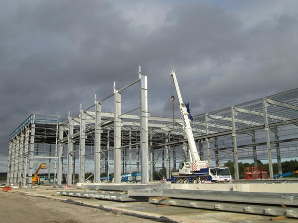 Steel for the MBT is erected by a crane positioned within the building's footprint