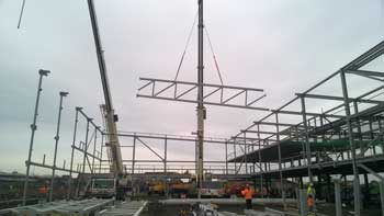 One of the five trusses that form the central zone is lifted into place