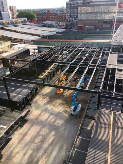 An independent steel roof structure covers the containers